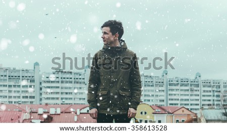 Young man in jacket in winter time on a rooftop with snow - stock photo