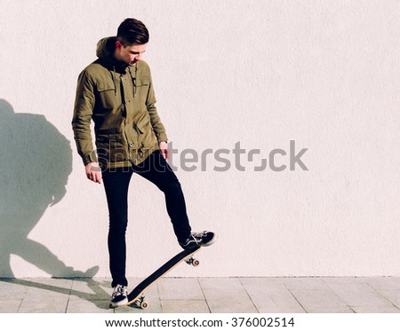 Young man in jacket on the skateboard on street - stock photo