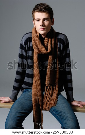 Young man in jeans sitting chair over a grey  - stock photo