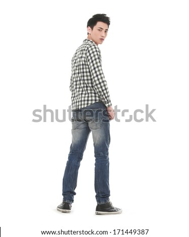 Young man in jeans standing back
