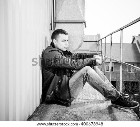young man in leather jacket sitting at metallic warehouse rooftop