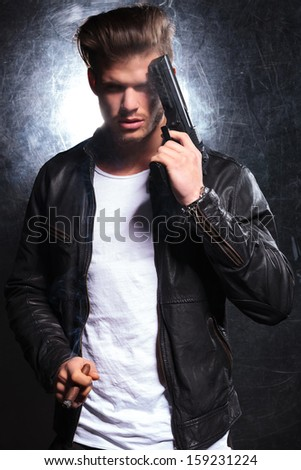 young man in leather jacket smoking a cigar and holding a pistol against his head