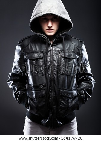 Young man in leather jacket with a hood on darkness background - stock photo
