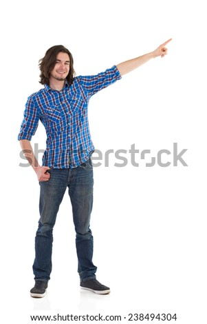 Young man in lumberjack shirt showing something. Handsome young man standing with arm raised, pointing and looking at camera. Full length studio shot isolated on white. - stock photo