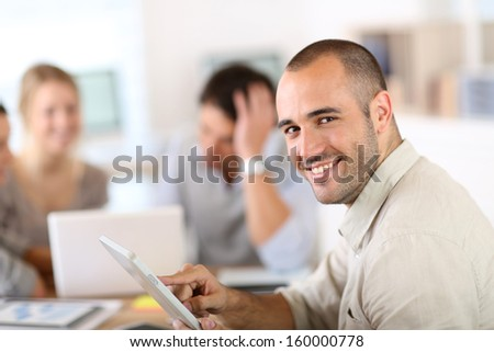 Young man in office working on digital tablet - stock photo