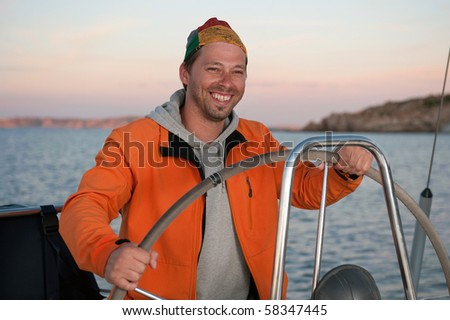 young man in orange jacket holding the steering wheel on the yacht during vacation - stock photo