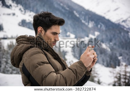 Young man in outerwear taking photo of landscape - stock photo