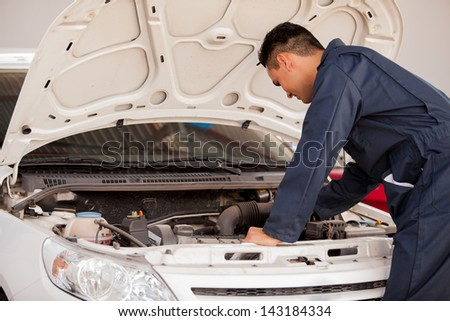 Young man in overall working on a car engine at an auto shop - stock photo
