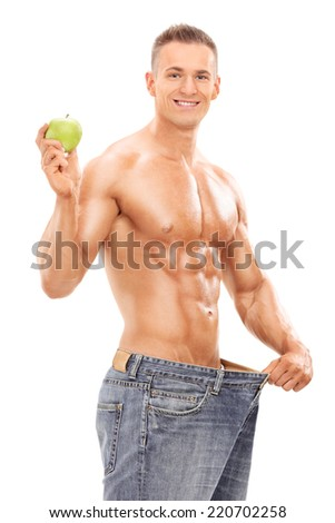 Young man in oversized jeans holding an apple isolated on white background - stock photo