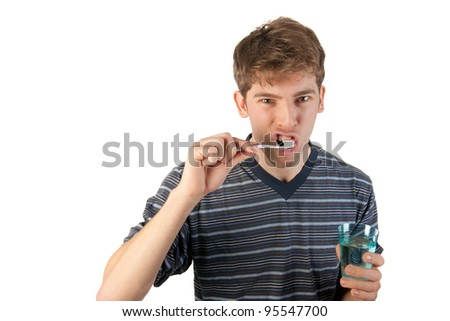 Young man in pajamas is brushing his teeth - stock photo