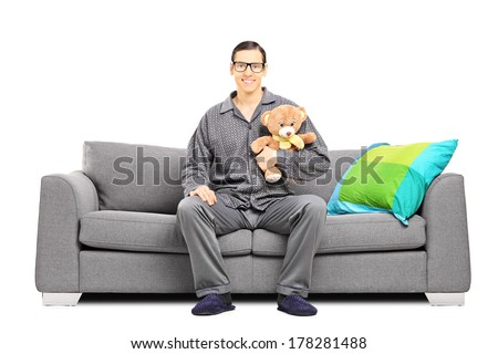 Young man in pajamas sitting on a sofa and holding a teddy bear isolated on white background