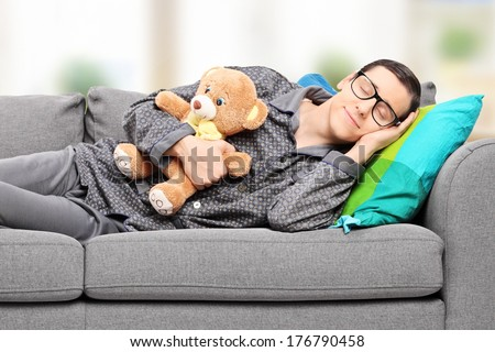 Young man in pajamas sleeping on sofa at home with teddy bear  - stock photo