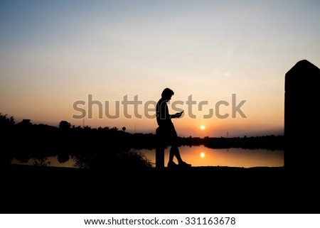 Young man in park using a mobile phone - stock photo
