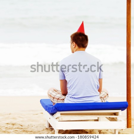 Young man in party hat sitting on beach bed under umbrella near sea - stock photo