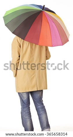Young man in raincoat back portrait with colorful umbrella. - stock photo