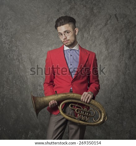 Young man in red suit and glasses. Hipster with musical pipe. - stock photo