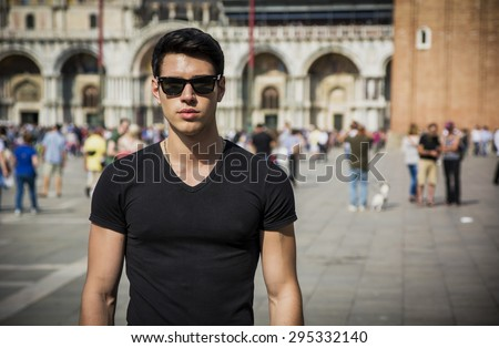 Young Man in San Marco Square in Venice, Italy, wearing black t-shirt and sunglasses - stock photo