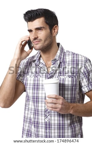 Young man in shirt talking on mobilephone, drinking coffee, looking away.