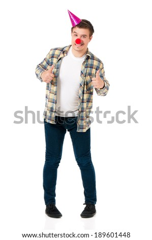 Young man in shirt with red clown nose and birthday cap, isolated on white background - stock photo