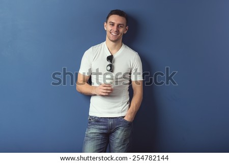 Young man in shorts and white t-shirt is smiling standing near the wall with glasses and coffee - stock photo