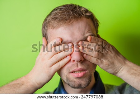 Young man in showing fatigue, sleepy, sleepy, closes his eyes with his hands. gesture. photo shoot. - stock photo