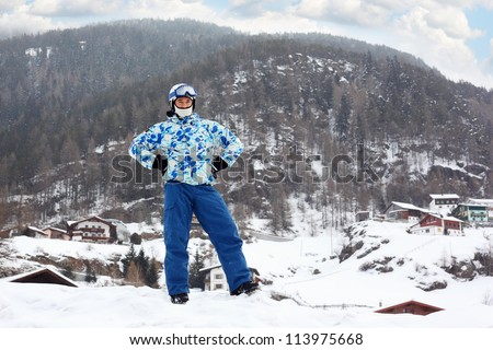 Young man in ski helmet and goggles on mountain at snowy winter. - stock photo