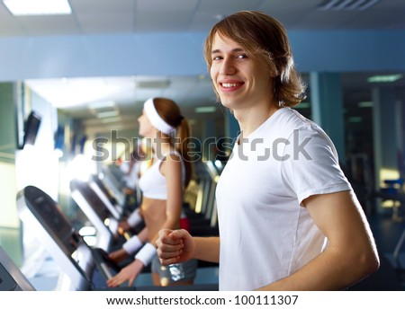 Young man in sport wear doing sport in gym