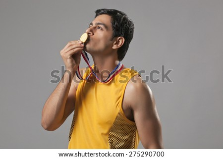 Young man in spots wear kissing gold medal isolated over gray background - stock photo