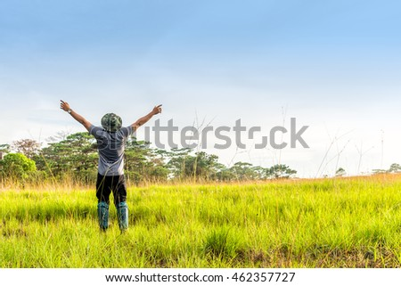 Young man in spreading hand in green meadow.