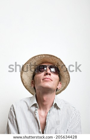 Young man in straw hat and sunglasses look up. copy space top