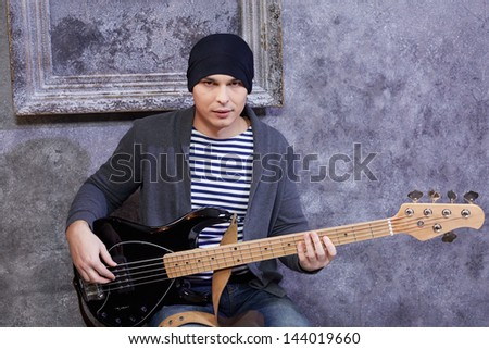 Young man in striped vest and knitted jacket sits with guitar near grey scuffed wall - stock photo