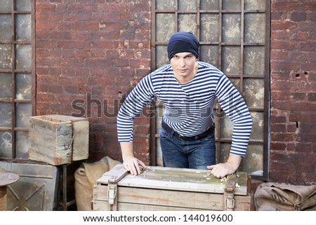 Young man in striped vest stands, leaning his hands on wooden chest - stock photo
