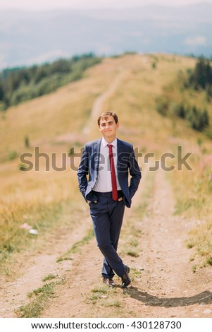 Young man in stylish suit standing on trail through summer field with hills at background - stock photo