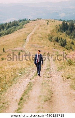 Young man in stylish suit walking on trail by summer field with hills at background - stock photo