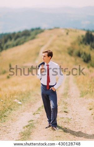 Young man in stylish suit walking on trail by summer field with his blazer over shoulder. Forest hills at background - stock photo
