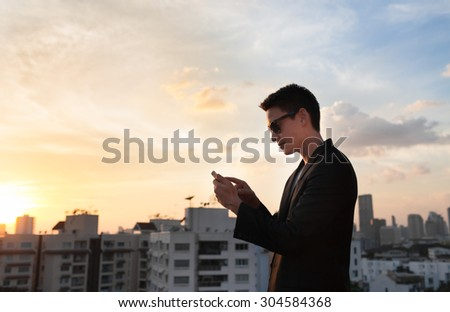 Young man in suit connecting with his smartphone in the city.  - stock photo