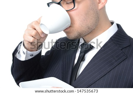 Young man in suit drinking coffee isolated