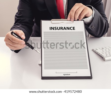 young man in suit in his office showing an insurance policy and pointing with a pen where the policyholder must to sign - stock photo