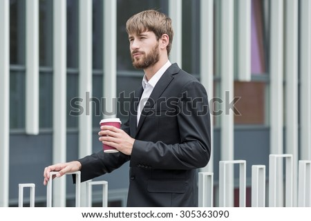 Young man in suit is holding cup of coffee - stock photo