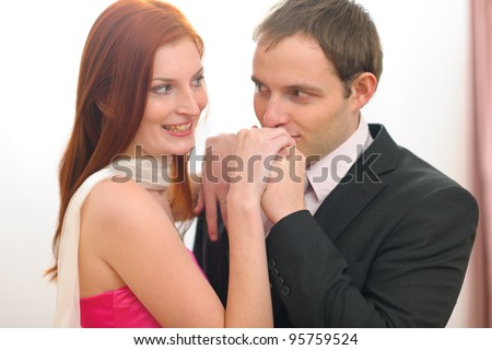 Young man in suit kissing hands of red hair woman in evening dress