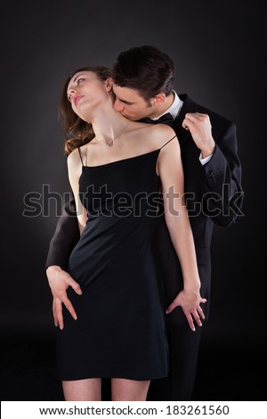 Young man in suit kissing woman on neck while removing dress strap from her shoulder isolated over black background - stock photo
