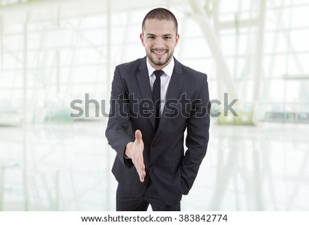 young man in suit offering to shake the hand at the office - stock photo