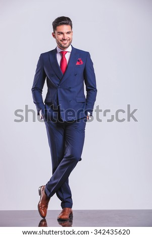 young man in suit posing with legs crossed while having hands in pockets - stock photo