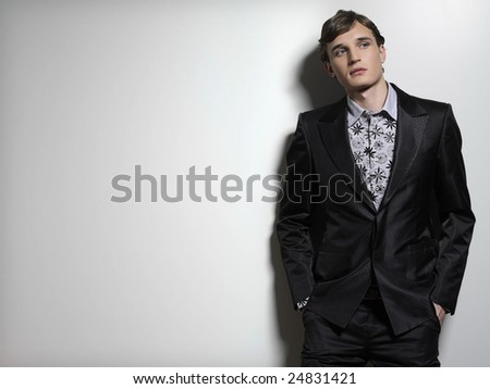 young man in suit standing near the wall studio shot - stock photo
