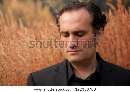 young man in suit, with black hair,looking down and thinking about problems - stock photo