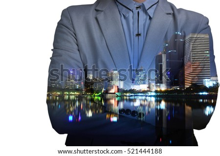 Young man in suit with fold arms on abstract illuminated night city background. Double exposure