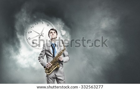 Young man in suit with saxophone in hands