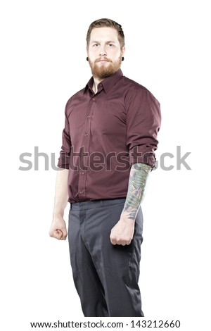 Young man in suit with tattoos against white background looking tough - stock photo