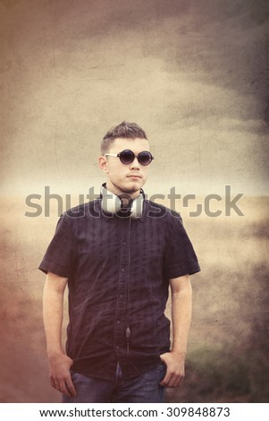 Young man in sunglasses and earphones at countryside outdoor. Photo in old color image style.