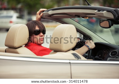Young man in sunglasses driving convertible car - stock photo